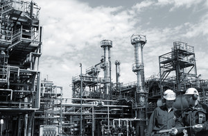 two refinery workers with large industrial refinery in background