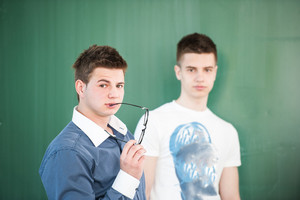 Two school students standing in front of a blackboard