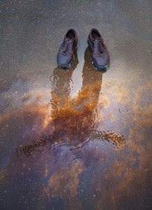 Two shoes in puddle with the reflection of a man.
