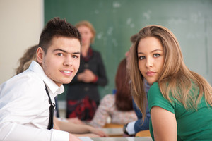 Two sitting students posing in a classroom