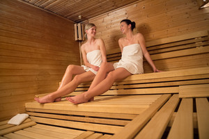 Two women chatting while relaxing on wooden bench at sauna