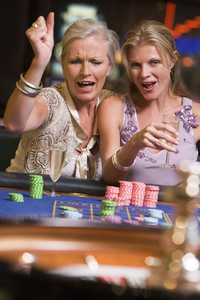 Two women gambling at roulette table in casino