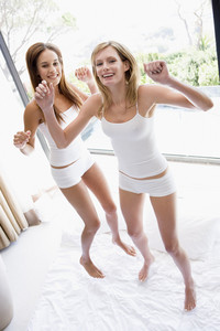 Two women jumping on bed smiling
