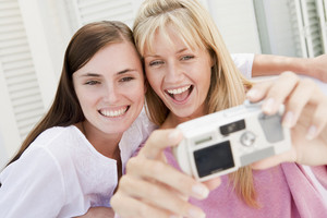 Two women on patio using digital camera smiling