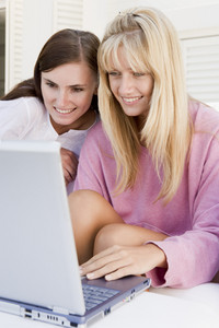 Two women on patio using laptop smiling