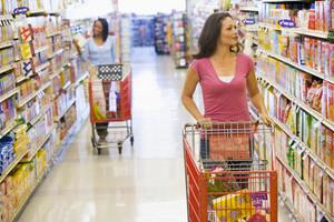 Two women pushing trolleys along supermarket aisle