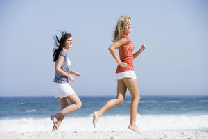 Two women running along beach with ocean in background