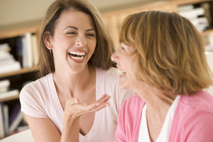 Two women sitting in living room talking and laughing