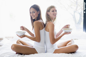 Two women sitting on bed eating cereal smiling