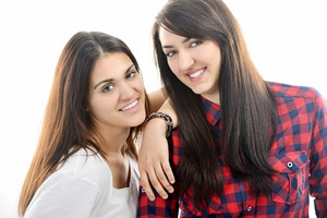Two young beautiful caucasian smiling girls leaning on each other isolated on white