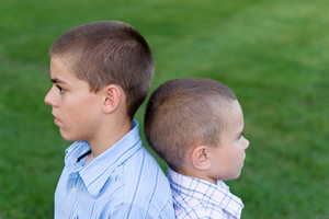Two young boys sitting back to back outdoors.