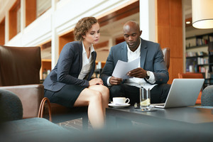 Two young business people with papers meeting in hotel lobby. African businessman and caucasian business woman sitting together at a cafe reading contract documents.