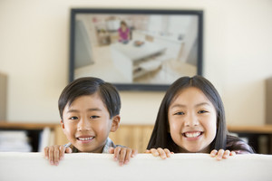 Two young children in living room with flat screen television smiling