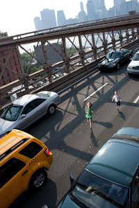Two young children running wild on the Brooklyn Bridge in between traffic.
