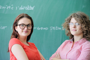 Two young girls with glasses standing in front of green blackboard