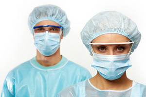 Two young surgeons in masks isolated on white