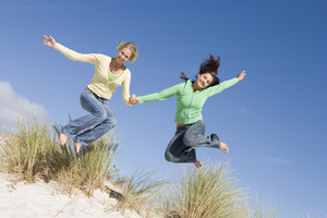 Two young woman in mid-air leap at beach