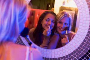 Two young women applying makeup in a nightclub bathroom