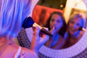 Two young women applying makeup in a nightclub bathroom