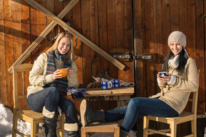 Two young women enjoy tea winter cottage wooden sunny outdoor
