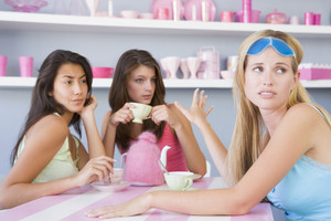 Two young women enjoying a tea party while one sits apart wearing a gel eye mask