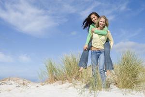 Two young women having piggyback fun in dunes