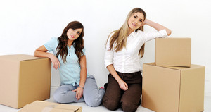 Two young women leaning on cardboard boxes