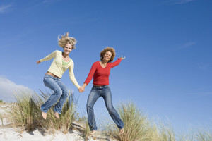 Two young women leaping in air at beach