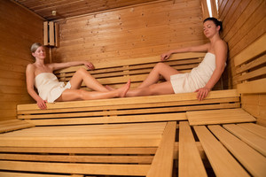 Two young women relaxing on wooden benches in sauna