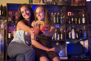 Two young women sitting on a bar counter, toasting the camera
