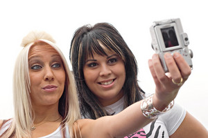 Two young women taking pictures of themselves with a digital camera.