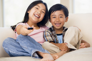 Two youngchildren in living room with remote control smiling