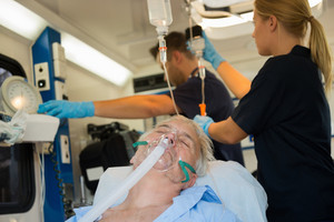 Unconscious senior patient with oxygen mask in ambulance car