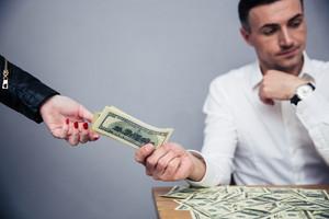 Unhappy man giving money to woman
