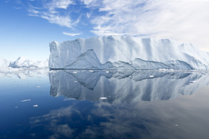 Unique, sunlit iceberg reflected in still water