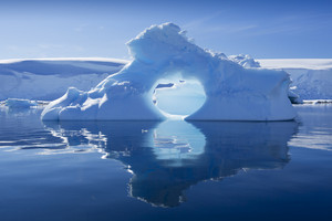 Unique, sunlit iceberg with a hole through it