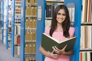 University student studying in library holding book