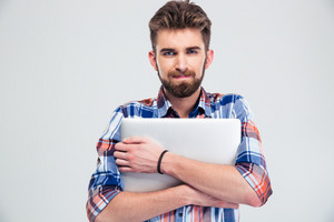 Unshaved handsome man holding laptop