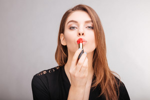 uwing and demonstrating red lipstick on her lips