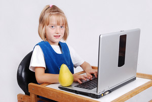 Very cute blond girl with laptop on desk isolated