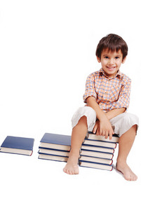 Very cute white kid sitting on books isolated