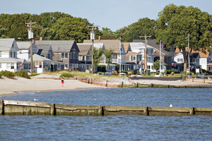 View of the New England coastline with a long row of beach cottages.