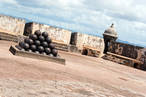 View of the upper interior of El Morro fort located in Old San Juan Puerto Rico.  There is a large pile of canon balls in a pyramid shape.