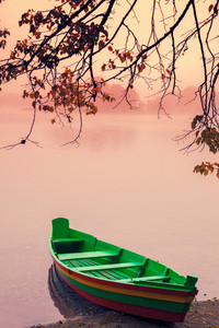Autumn misty morning. Wooden boat on the river bank.