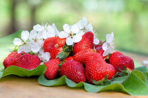 Strawberries on leaves on wooden table