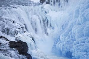 Waterfall rushing through thick ice