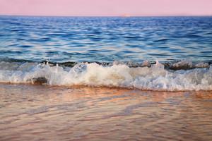 Wave hitting a beach at sunrise