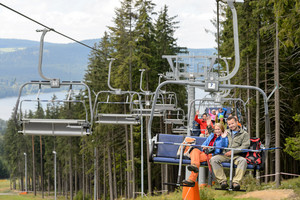 Waving young people sitting on chairlift going through forest