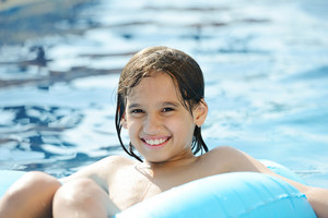 Wet kid having happy time on summer swimming pool