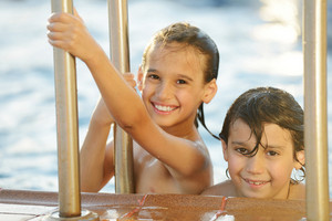 Wet kids having happy time on summer swimming pool